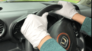 Gloved Hands on Steering Wheel while driving a car
